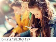 Купить «happy teenage friends with smartphones outdoors», фото № 28363197, снято 21 мая 2016 г. (c) Syda Productions / Фотобанк Лори