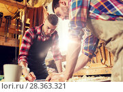 carpenters with ruler and blueprint at workshop. Стоковое фото, фотограф Syda Productions / Фотобанк Лори