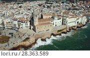 Купить «Aerial view of Sitges small town with church on Mediterranean coastline, Spain», видеоролик № 28363589, снято 27 апреля 2018 г. (c) Яков Филимонов / Фотобанк Лори