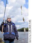 Купить «Рыбак поймал четыре воблы на фидерную удочку. Фокус на рыбе», эксклюзивное фото № 28369145, снято 21 апреля 2018 г. (c) Игорь Низов / Фотобанк Лори