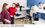 Купить «Polite attractive girl friendly meeting new female neighbor in hostel dormitory», фото № 28369605, снято 22 марта 2018 г. (c) Яков Филимонов / Фотобанк Лори