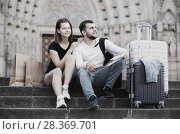 Купить «Emotional man and woman sitting at stairs with map», фото № 28369701, снято 25 мая 2017 г. (c) Яков Филимонов / Фотобанк Лори