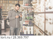 Купить «young man customer examining various glue tubes in store», фото № 28369797, снято 5 апреля 2017 г. (c) Яков Филимонов / Фотобанк Лори