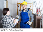 Купить «Constructor with spatula is talking to client», фото № 28369857, снято 3 июня 2017 г. (c) Яков Филимонов / Фотобанк Лори