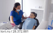 Купить «female dentist with kid patient at dental clinic», видеоролик № 28372881, снято 26 апреля 2018 г. (c) Syda Productions / Фотобанк Лори