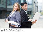 Купить «Portrait of couple professionals who are posing with laptop and folder», фото № 28373113, снято 20 августа 2017 г. (c) Яков Филимонов / Фотобанк Лори