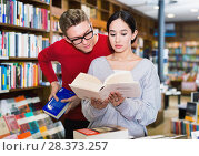 Купить «Girl reading book in bookstore while guy looking at her book over her shoulder», фото № 28373257, снято 18 января 2018 г. (c) Яков Филимонов / Фотобанк Лори