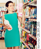 Купить «Charming female want to buying cleaners in bottle», фото № 28391205, снято 6 июня 2017 г. (c) Яков Филимонов / Фотобанк Лори