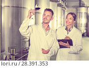 Купить «Man and woman employees on winery manufactory», фото № 28391353, снято 22 июля 2018 г. (c) Яков Филимонов / Фотобанк Лори