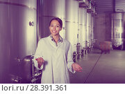 Купить «Female in uniform standing in winery compartment», фото № 28391361, снято 15 сентября 2019 г. (c) Яков Филимонов / Фотобанк Лори