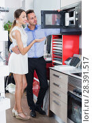 Купить «Smiling woman and husband choosing new microwave», фото № 28391517, снято 15 июня 2017 г. (c) Яков Филимонов / Фотобанк Лори