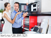Купить «Couple choosing microwave in household appliance section», фото № 28391521, снято 15 июня 2017 г. (c) Яков Филимонов / Фотобанк Лори