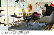 Купить «Portrait of happy girl sitting in comfortable office chair bought in furnishings store», видеоролик № 28398229, снято 28 марта 2018 г. (c) Яков Филимонов / Фотобанк Лори