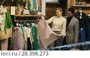 Купить «Couple is choosing jeans clothes for her in the clothes store.», видеоролик № 28398273, снято 27 марта 2018 г. (c) Яков Филимонов / Фотобанк Лори