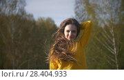 Купить «Young happy woman posing on the background of trees», видеоролик № 28404933, снято 18 августа 2019 г. (c) Константин Шишкин / Фотобанк Лори