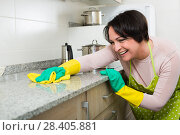 Купить «Positive housewife polishing kitchen surfaces», фото № 28405881, снято 21 июля 2018 г. (c) Яков Филимонов / Фотобанк Лори