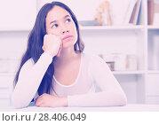 Купить «Gloomy girl sitting at the table», фото № 28406049, снято 30 мая 2017 г. (c) Яков Филимонов / Фотобанк Лори
