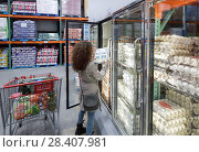 Купить «Woman picking a crate of omega-3 eggs from a fridge at Costco Wholesale membership warehouse store food section. British Columbia, Canada.», фото № 28407981, снято 13 марта 2018 г. (c) age Fotostock / Фотобанк Лори