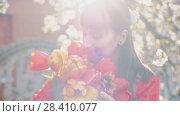 Купить «Woman smelling spring flowers», видеоролик № 28410077, снято 2 мая 2018 г. (c) Илья Шаматура / Фотобанк Лори