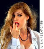 Купить «Woman eating berry. Pin up girl wearing unbuttoned blouse and bra.», фото № 28410189, снято 25 мая 2018 г. (c) Gennadiy Poznyakov / Фотобанк Лори