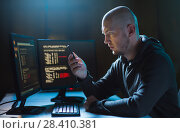 Купить «hacker with smartphone and computers in dark room», фото № 28410381, снято 9 ноября 2017 г. (c) Syda Productions / Фотобанк Лори
