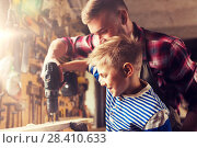 Купить «father and son with drill working at workshop», фото № 28410633, снято 14 мая 2016 г. (c) Syda Productions / Фотобанк Лори