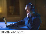 hacker in headset typing on laptop in dark room. Стоковое фото, фотограф Syda Productions / Фотобанк Лори