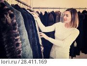 Купить «Young female customer examining best fur coats», фото № 28411169, снято 3 июня 2020 г. (c) Яков Филимонов / Фотобанк Лори