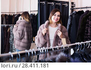Купить «woman trying on fur coat in women's cloths store», фото № 28411181, снято 14 февраля 2020 г. (c) Яков Филимонов / Фотобанк Лори