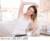 Smiling woman is doing morning exercises for her waist near laptop. Стоковое фото, фотограф Яков Филимонов / Фотобанк Лори
