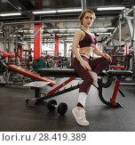 Купить «The girl in the gym with a dumbbell, in a beautiful sports uniform», фото № 28419389, снято 25 апреля 2018 г. (c) Restyler Viacheslav / Фотобанк Лори