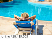 Купить «Woman in a straw hat relaxing near a luxurious summer pool, concept time to travel», фото № 28419505, снято 16 апреля 2018 г. (c) Happy Letters / Фотобанк Лори