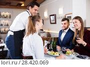 Купить «Waiter bringing dishes to guests», фото № 28420069, снято 7 ноября 2017 г. (c) Яков Филимонов / Фотобанк Лори