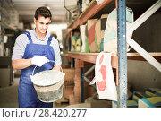 Купить «Salesman is placing buckets for putty», фото № 28420277, снято 26 июля 2017 г. (c) Яков Филимонов / Фотобанк Лори