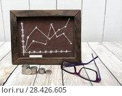 Купить «Российские рубли, очки и доска с нарисованным графиком. Динамика роста цен», фото № 28426605, снято 17 мая 2018 г. (c) Наталья Осипова / Фотобанк Лори