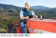 Купить «Confident male owner of vineyard driving tractor outdoors in sunny day», фото № 28426961, снято 22 января 2018 г. (c) Яков Филимонов / Фотобанк Лори