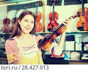 Купить «Teenage girl choosing classical violin», фото № 28427013, снято 20 августа 2018 г. (c) Яков Филимонов / Фотобанк Лори