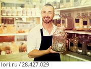 Купить «Happy man holding glass can with dried herbs», фото № 28427029, снято 5 июля 2020 г. (c) Яков Филимонов / Фотобанк Лори