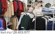 Купить «Happy teen girl looking for new clothing with her mum during family shopping», видеоролик № 28433977, снято 26 апреля 2018 г. (c) Яков Филимонов / Фотобанк Лори