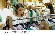 Купить «Young woman looking for interesting cloth in textile shop», видеоролик № 28434017, снято 27 марта 2018 г. (c) Яков Филимонов / Фотобанк Лори