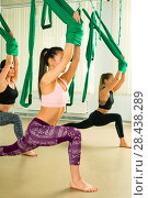 Купить «Young woman performing aerial yoga exercise», фото № 28438289, снято 13 мая 2018 г. (c) Владимир Мельников / Фотобанк Лори