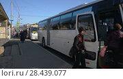 Купить «Пассажиры садятся в белый междугородний маршрутный автобус», видеоролик № 28439077, снято 19 мая 2018 г. (c) А. А. Пирагис / Фотобанк Лори