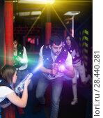 Купить «Emotional guy playing laser tag in colorful beams», фото № 28440281, снято 25 апреля 2018 г. (c) Яков Филимонов / Фотобанк Лори