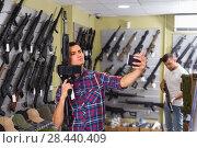 Купить «Young man is taking selfie on phone with air gun», фото № 28440409, снято 4 июля 2017 г. (c) Яков Филимонов / Фотобанк Лори