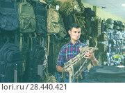 Купить «Man choosing textile backpack gun in military shop», фото № 28440421, снято 4 июля 2017 г. (c) Яков Филимонов / Фотобанк Лори