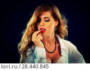 Купить «Woman eating berry. Pin up girl wearing unbuttoned blouse and bra.», фото № 28440845, снято 24 мая 2018 г. (c) Gennadiy Poznyakov / Фотобанк Лори