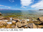 Купить «Lake Baikal. Stony coast of the island of Olkhon on a sunny day. Transparent water splashes on rocks near the shore», фото № 28442181, снято 19 мая 2018 г. (c) Виктория Катьянова / Фотобанк Лори