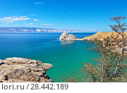 Купить «Baikal Lake on a sunny May day. A view of the natural landmark - Shamanka Rock from the coast of Olkhon Island. On the larch trees on the shore begins to appear young green needles», фото № 28442189, снято 19 мая 2018 г. (c) Виктория Катьянова / Фотобанк Лори