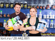 Купить «Happy young sporty people standing in store, holding big can of sport nutrition», фото № 28442881, снято 12 апреля 2018 г. (c) Яков Филимонов / Фотобанк Лори
