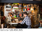Купить «male worker sewing stitches on belt in leather workshop», фото № 28450305, снято 12 декабря 2018 г. (c) Яков Филимонов / Фотобанк Лори